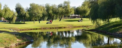 Golfcursus door een vijver bij een exclusief park als het plaatsen stock afbeelding