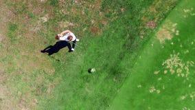 Golfcursus met een mannelijke speler die in een mening hierboven raken van stock video