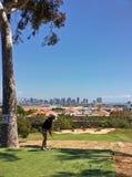 Golfcursus met een mening van stadshorizon stock foto's