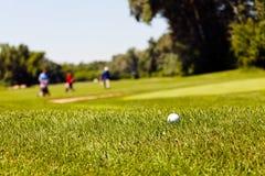Golfcursus met spelers stock afbeeldingen