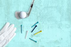 Golf club, golf ball and tees on structured surface in turquoise royalty free stock photo