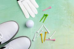 Golf ball, golf shoes and tees on a base in light green. From above, free text space stock photos
