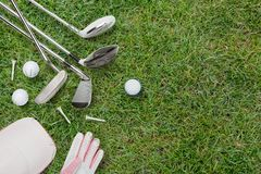 Golf clubs, golf balls, golf glove and cap on grass stock images