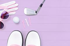 Golf accessories for women on a wooden surface in purple stock photos