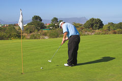 Golfer. Hitting the ball into the hole. Ball in motion Stock Photography