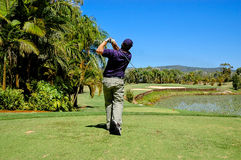 Golfer. Driving golf ball over a water hazard onto the green of a par 3 hole Royalty Free Stock Images