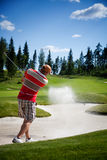 Golfer. Male golfer shooting a golf ball from sand Stock Photography