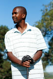 Golfer. An african golfer holding his golf club and look aside Stock Images