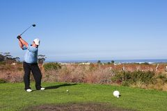 Golfer #58. A golfer playing golf on a tee box.  Movement on golf club, but head is in focus Royalty Free Stock Image
