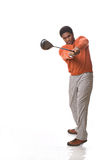 Golfer. Handsome African-American man swings a golf club Royalty Free Stock Image