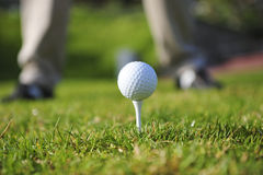 Golfer in action. A golfer in action on a practice range. Focus on the ball and tee, with golfers legs faded out in the background Stock Photography