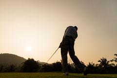 Golfer action while sunset. Silhouette shot of golfer swing action Royalty Free Stock Photography
