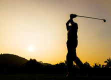 Golfer action while sunset. Silhouette shot of golfer swing action Royalty Free Stock Photo
