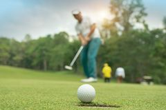 Golfer action to win after long putting golf ball on the green golf. Lens flare on sun set evening time stock photo