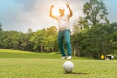 Golfer action to win after long putting golf ball on the green golf stock photography
