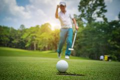Golfer action to win after long putting golf ball on the green golf. Lens flare on sun set evening time stock images