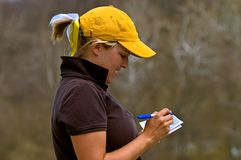 Golfer adding scorecard. Emotional female college golfer adding scorecard after a tournament round Stock Image
