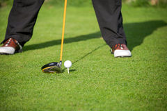 Golfer addresses golf ball. With driver in tee box Stock Image