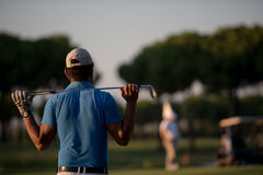 Golfer from back at course looking to hole in distance. Golfer  from back looking to ball and  hole in distance, handsome middle eastern golf player portrait Stock Image