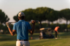 Golfer from back at course looking to hole in distance. Golfer  from back looking to ball and  hole in distance, handsome middle eastern golf player portrait Royalty Free Stock Images