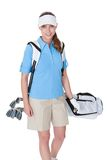 Golfer with a bag of clubs. Attractive female golfer in golf clothing with a bag of clubs selecting an iron Stock Photography