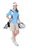 Golfer with a bag of clubs. Attractive female golfer in golf clothing with a bag of clubs selecting an iron isolated on white stock photography