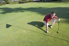 Golfer Bends to Mark Ball - Horizontal. Male golfer bends down to mark golf ball. He is smiling at camera. Horizontally framed photo Royalty Free Stock Photos