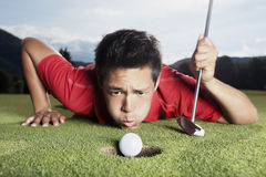 Golfer blowing ball into cup. Royalty Free Stock Photos