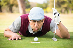 Golfer blowing ball in the hole Stock Image