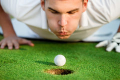 Golfer blowing in the ball. Golfer lying on grass and blowing in the ball,  just need to give it a little help Stock Photography