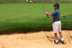 Golfer in the bunker. Golfer in the sand bunker. Happy because he landed the ball right next to the hole Royalty Free Stock Images