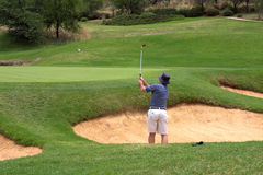 Golfer in the bunker. Golfer hitting the ball out of the sand bunker straight onto the green. The golf ball is flying in the air Stock Photo