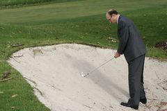 Golfer in Business Clothes. A golfer dressed in a business suit is about to hit a ball out of a sand trap.  Theme: conducting business on a golf course Royalty Free Stock Photography