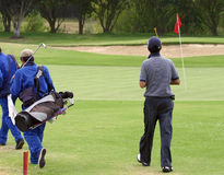 Golfer and caddies Royalty Free Stock Photos