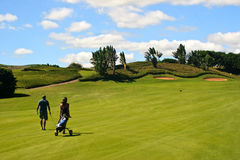 Golfer and caddy girl walking Stock Images