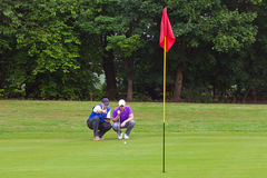 Golfer and caddy reading the line of putt Stock Image