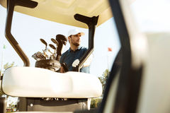 Golfer in cap standing at the golf cart Royalty Free Stock Images