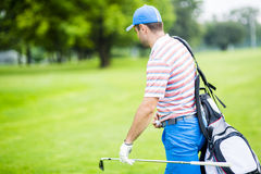Golfer carrying his equipment Stock Images