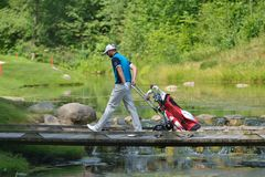 Golfer with cart traverses the river Stock Photography