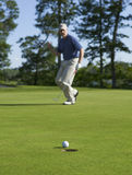 Golfer celebrates sinking putt on green. A defocused golfer celebrates sinking a putt on a green Stock Photography