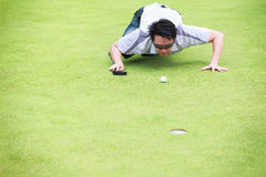 Golfer checking line of putt Royalty Free Stock Photo