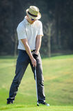 Golfer is chipping a golf ball onto the green with driver golf c Stock Photo