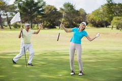 Golfer couple celebrating success. While standing on field Royalty Free Stock Photography