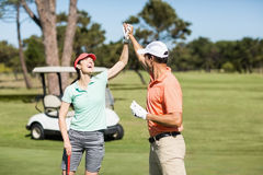 Golfer couple giving high five Royalty Free Stock Photography