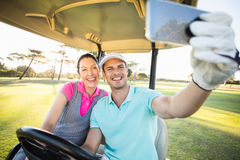 Golfer couple taking selfie while sitting in golf buggy Stock Images