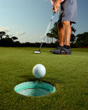 Golfer on a course golfing. Golfer putting ball in hole on golf course Stock Image