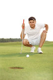 Golfer crouching and eyeing up putt Royalty Free Stock Photography