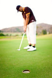 Golfer doing putt Stock Photos