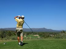 Golfer driving golf ball Stock Photo