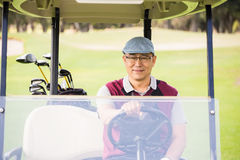 Golfer driving a golf buggy Royalty Free Stock Photography
